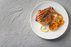 Plate with delicious grilled steak, pepper and sauce on textured background royalty free stock images