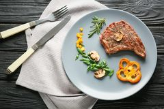 Plate with delicious grilled steak and pepper on table stock image
