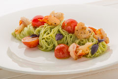 Plate of delicious italian pasta: spaghetti with shrimps and cherry Royalty Free Stock Images