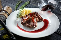 Plate with delicious ribs, bottle of wine and glasses Stock Photos