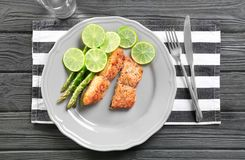Plate with delicious salmon, sliced lime. And asparagus on wooden table royalty free stock images