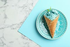 Plate with delicious spirulina ice cream cone on marble table, top view.