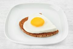 Plate with delicious sunny side up egg and bread slice. On wooden background Royalty Free Stock Photos