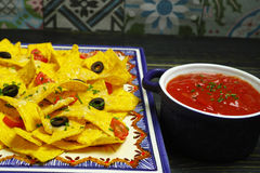 A plate of delicious tortilla nachos with melted cheese sauce, c Stock Images