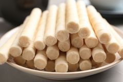 Plate with delicious wafer rolls on table, closeup. Sweet food royalty free stock images