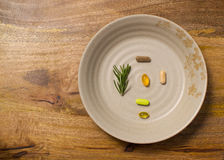 Plate of dietary supplements on aged wooden board Royalty Free Stock Images