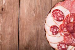 Plate with different sliced sausage on an old wooden table. With Stock Photos
