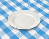 Plate or dish over blue checked tablecloth Royalty Free Stock Images