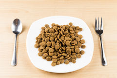 A plate of dog kibbles served on table with spoon and fork Royalty Free Stock Photos