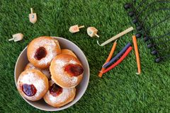 Plate of doughnuts and Hanukkah items outside on a grass backgro Royalty Free Stock Image