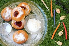 Plate of doughnuts and Hanukkah items outside on a grass backgro Stock Images