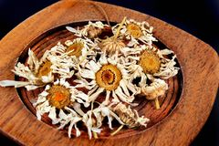 Plate with dried chamomile flowers on black background Stock Photo