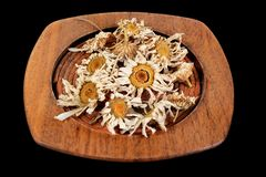 Plate with dried chamomile flowers Stock Images