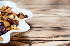 Plate of dried fruits on wooden table, Mix of nuts and berries: cashews, hazelnut, almonds, yellow, brown and blue royalty free stock photos