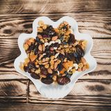 Plate of dried fruits on wooden table, Mix of nuts and berries: raisins, hazelnut, cashews, almonds, yellow, cranberries. Plate of dried fruits on wooden table stock photo