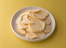 Plate of dried peach slices on a yellow table Royalty Free Stock Photos