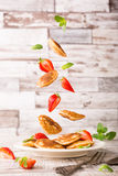 Plate with dutch mini pancakes called poffertjes and flying ingredients Stock Photos