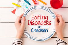Plate with `Eating Disorders in Children` sign in kid`s hands. Anorexia and bulimia problem - concept captured from above top view, flat lay. Crayons and child stock photo