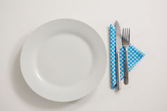 Plate with eating utensils and napkin. Overhead view of plate with eating utensils and napkin on table Royalty Free Stock Images