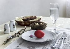 On a plate egg red color fork knife glass of water bread pepper salt nest easter Royalty Free Stock Images