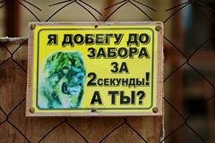 A plate about an evil dog guarding the house. The inscription in Russian ` I get to the fence in 2 seconds!  And you?`. Warning stock images
