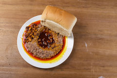 A plate of ewa agoyin and agege bread. A Nigerian staple meal consisting of bread and baked beans with red palm oil stew.Agoyin sauce Stock Photo