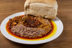 A plate of ewa agoyin and agege bread. A Nigerian staple meal consisting of bread and baked beans with Agoyin sauce Royalty Free Stock Photo