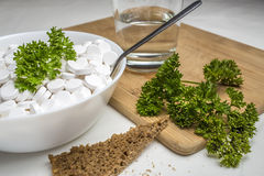 Plate filled with medical pills drugs is on the table with a spoon inside, next to the food Stock Photo