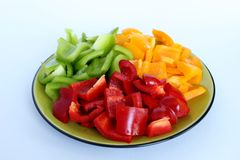 A plate filled with peppers in three colors and cut into squares Stock Images