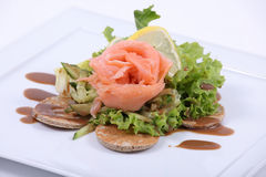 Plate of fine dining meal. Smoked salmon, served on yeasted pancakes and accompanied by cucumber Julienne and mixed lettuce leaves with a dill vinaigrette Stock Photography
