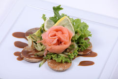 Plate of fine dining meal. Smoked salmon, served on yeasted pancakes and accompanied by cucumber Julienne and mixed lettuce leaves with a dill vinaigrette Stock Image