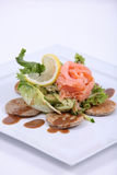 Plate of fine dining meal. Smoked salmon, served on yeasted pancakes and accompanied by cucumber Julienne and mixed lettuce leaves with a dill vinaigrette Stock Photo