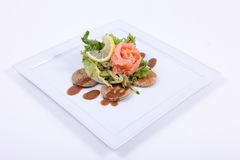 Plate of fine dining meal. Smoked salmon, served on yeasted pancakes and accompanied by cucumber Julienne and mixed lettuce leaves with a dill vinaigrette Royalty Free Stock Image
