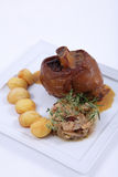 Plate of fine dining meal. Roast leg of lamb with thyme and garlic, served with onions braised in wine and cubed potatoes Royalty Free Stock Images