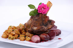 Plate of fine dining meal. Roast leg of lamb with thyme and garlic, served with onions braised in wine and cubed potatoes Stock Images