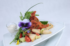 Plate of fine dining meal. A salad of young vegetable leaves and shoots served with bacon, garlic, cocktail tomatoes, toasted sunflower seeds and a creamy Stock Image