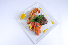 Plate of fine dining meal beef with lobster. Filet mignon of Limousin beef tenderloin on grilled lobster, baked in fresh sage and rosemary leaves and royalty free stock photography