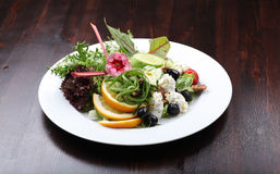 Plate of fine dining meal, fresh salad. Original salad with fresh rucola leaves, olives, orange Royalty Free Stock Images