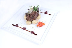 Plate of fine dining meal - Haunch of venison. Haunch of venison pan-fried on glowing chunks of volcanic lava and served with cheese dumplings filled with royalty free stock photos