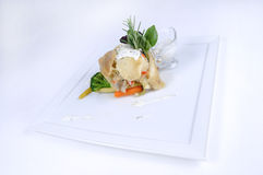 Plate of fine dining meal - lemon sole vegetables. Lemon sole baked in vegetable Julienne and mozzarella slices with a marinade of oil and pumpkin seeds and stock photography
