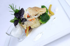 Plate of fine dining meal - lemon sole vegetables. Lemon sole baked in vegetable Julienne and mozzarella slices with a marinade of oil and pumpkin seeds and Stock Image