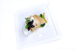 Plate of fine dining meal - lemon sole vegetables. Lemon sole baked in vegetable Julienne and mozzarella slices with a marinade of oil and pumpkin seeds and Royalty Free Stock Photo