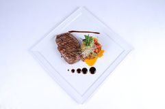 Plate of fine dining meal ostrich fillet salad. Tender ostrich fillet, rosy-baked and served on paprika pepperonata with a creamy fig and balsamic sauce Stock Photo