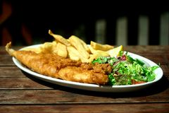 Plate of fish and chips . Plate of fish and chips with side serving of fresh salad Royalty Free Stock Photography