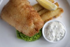 Plated fish and chips with mushy peas. A plate of fish and chips with mushy peas, tartare sauce and a lemon wedge royalty free stock photography