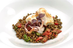 Plate of fish, squid braised with lentils. Gourmet fish dish, squid braised with tomatoes and lentils Royalty Free Stock Photos