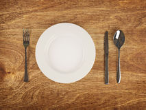 Plate and flatware on wooden table Stock Photos