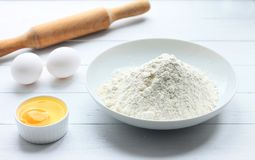A plate with flour, eggs, a rolling pin on a white wooden background. Pancakes ingredients. Egg in the bowl stock image