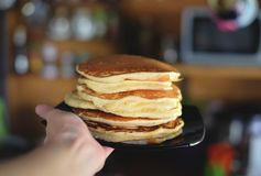 Plate with fluffy tasty pancakes in the hand stock photo