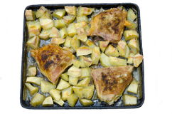 A plate with food. Three fried chicken thighs lie on a baking tray with cut potatoes Stock Photos